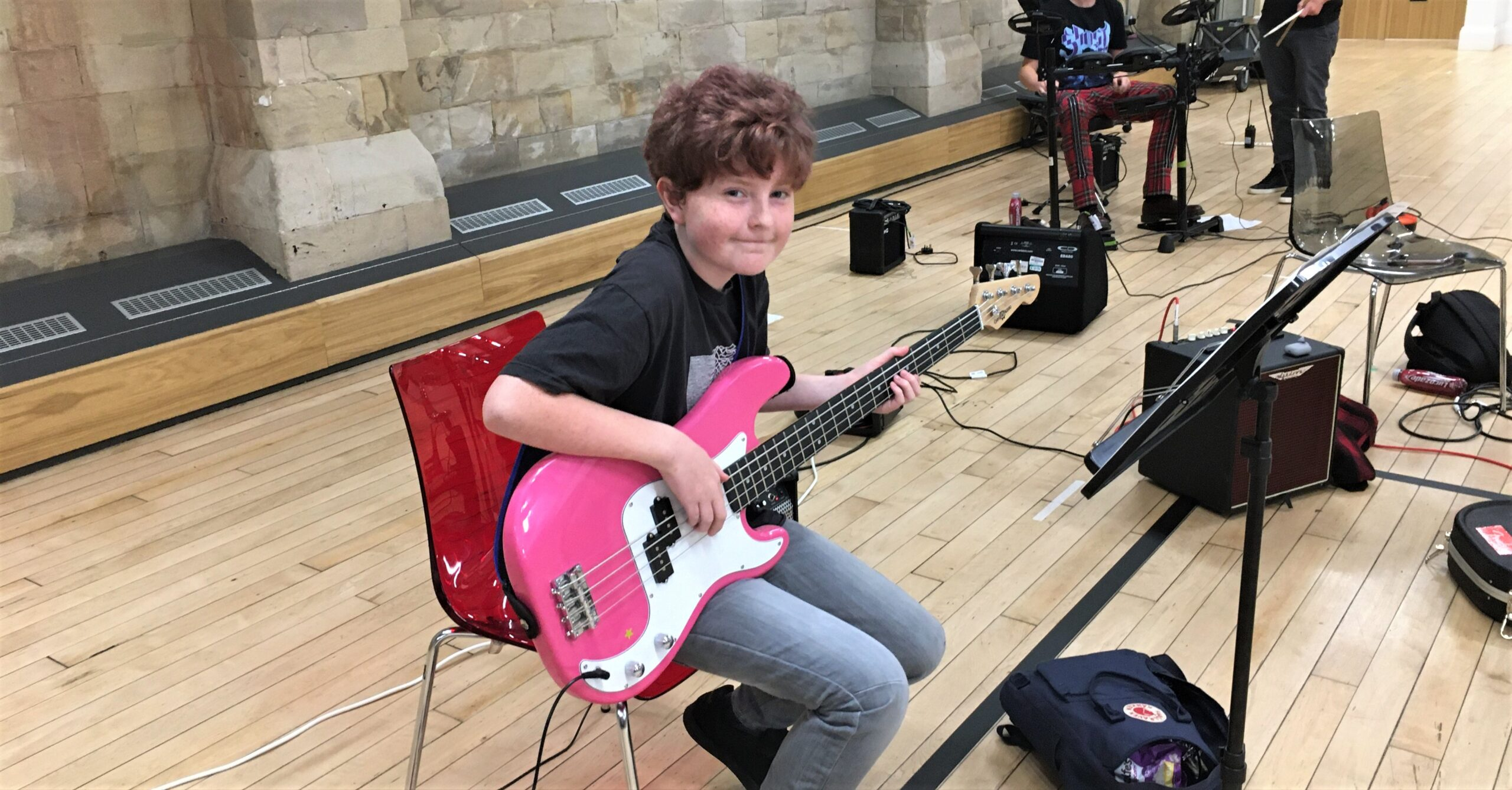 A boy looks at the camera whilst holding a pink bass guitar during a music session