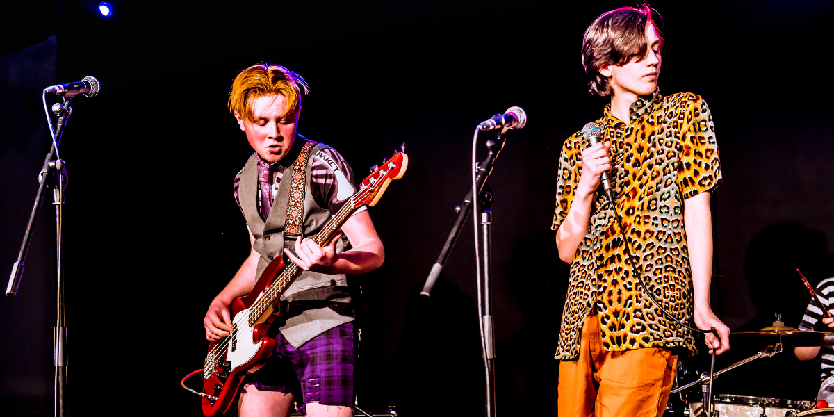 A photograph of two young people performing on a stage. One is playing bass guitar and the other is holding a mic.