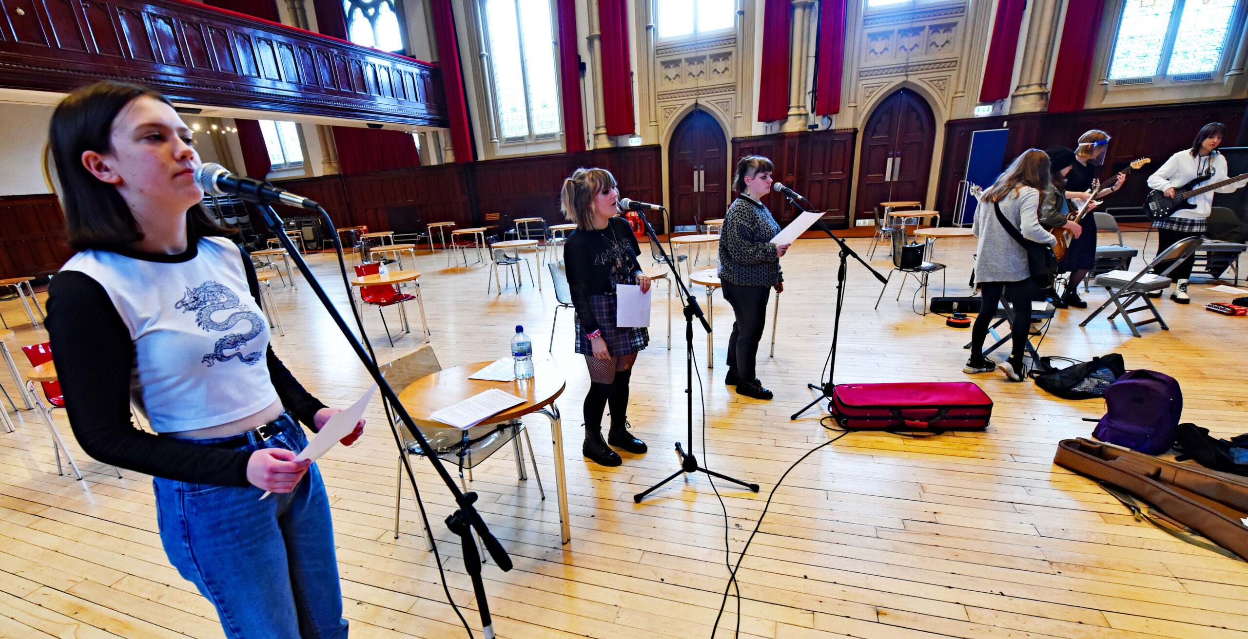 3 young people standing with mic stands in front of them in the main hall of Middlesbrough Town Hall