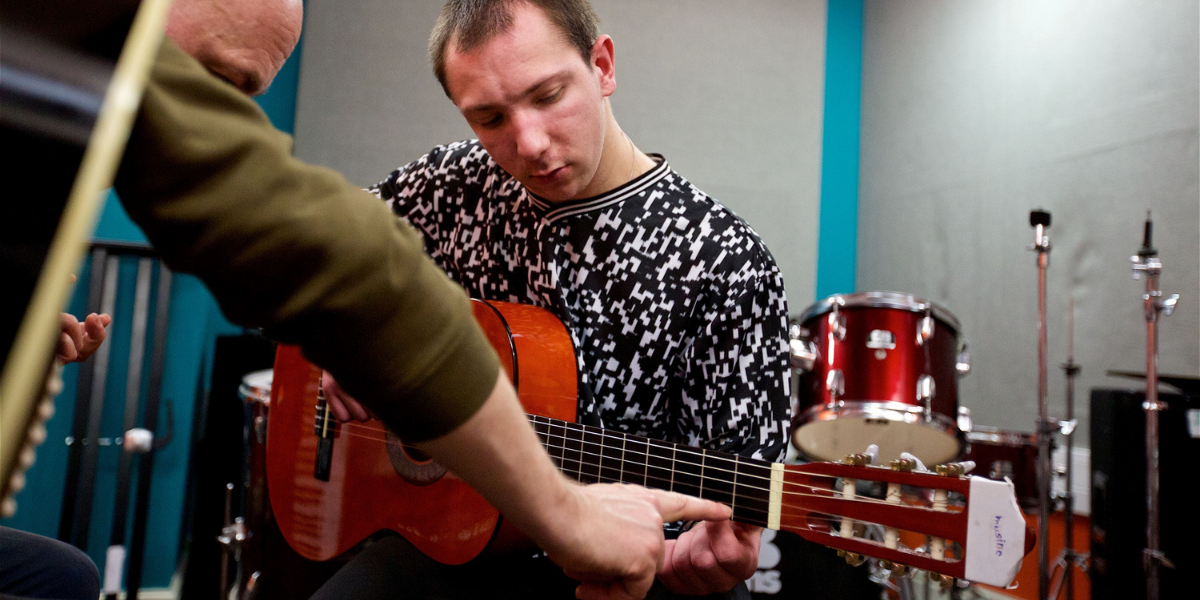 A music leader teaching a young man how to play guitar by pointing out a musical chord on the neck of the guitar.