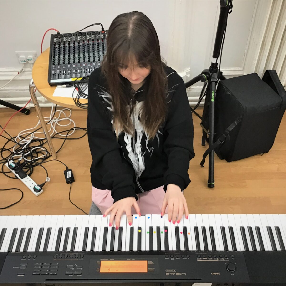 A girl sitting down and playing the piano keyboard
