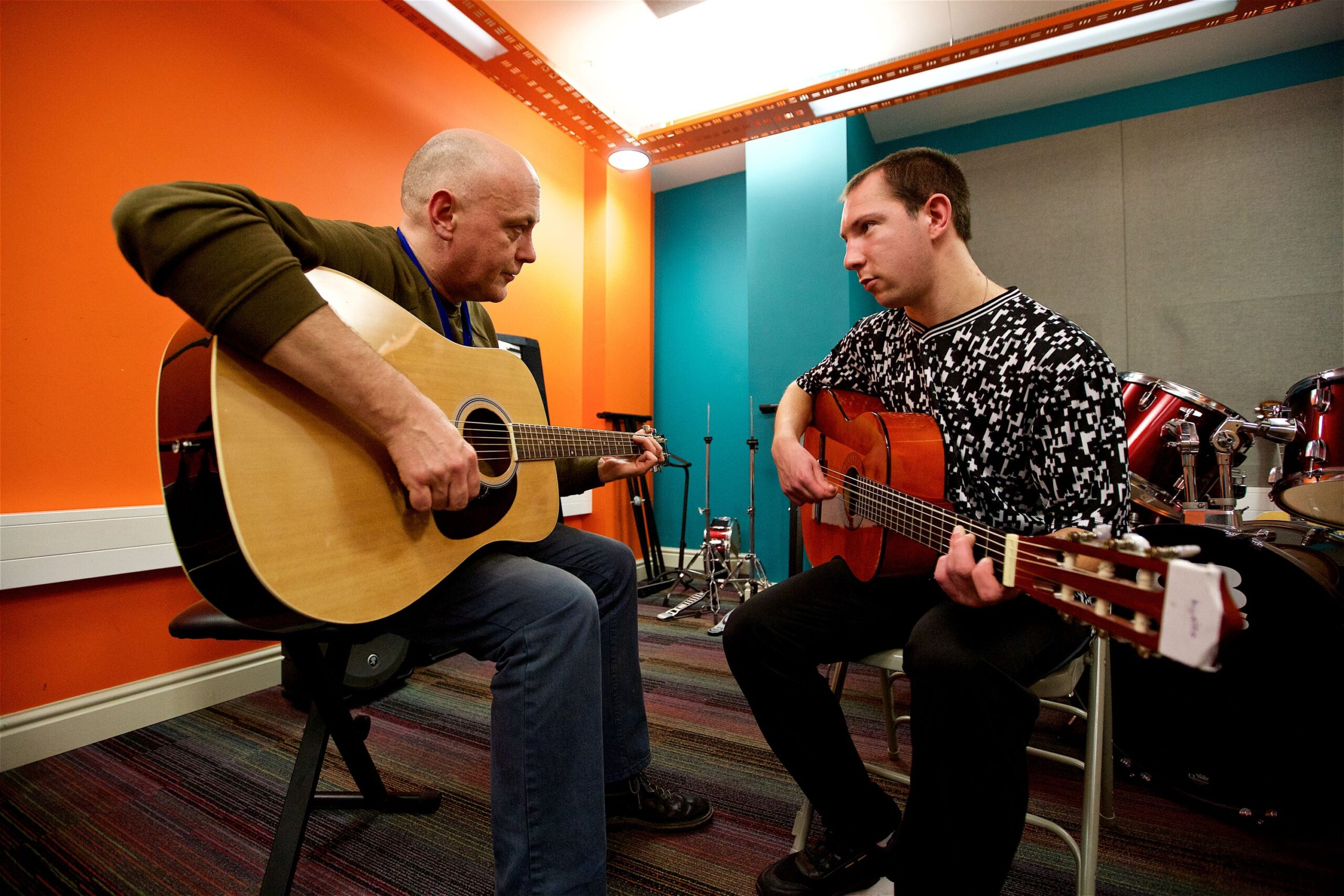 Two men sit facing each other with acoustic guitars