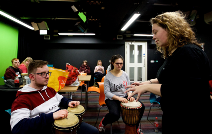 A female music leader instructs a young male participant on playing the bongo drums. In the background are another seated female participant and other participants observing the session.