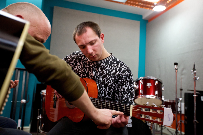 A music leader teaches a young male student to play guitar by pointing out where to place their fingers on the fretboard.