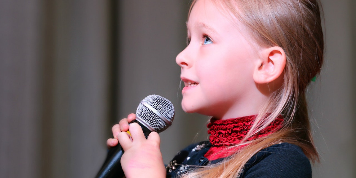 A young girl holding a mic and looking up