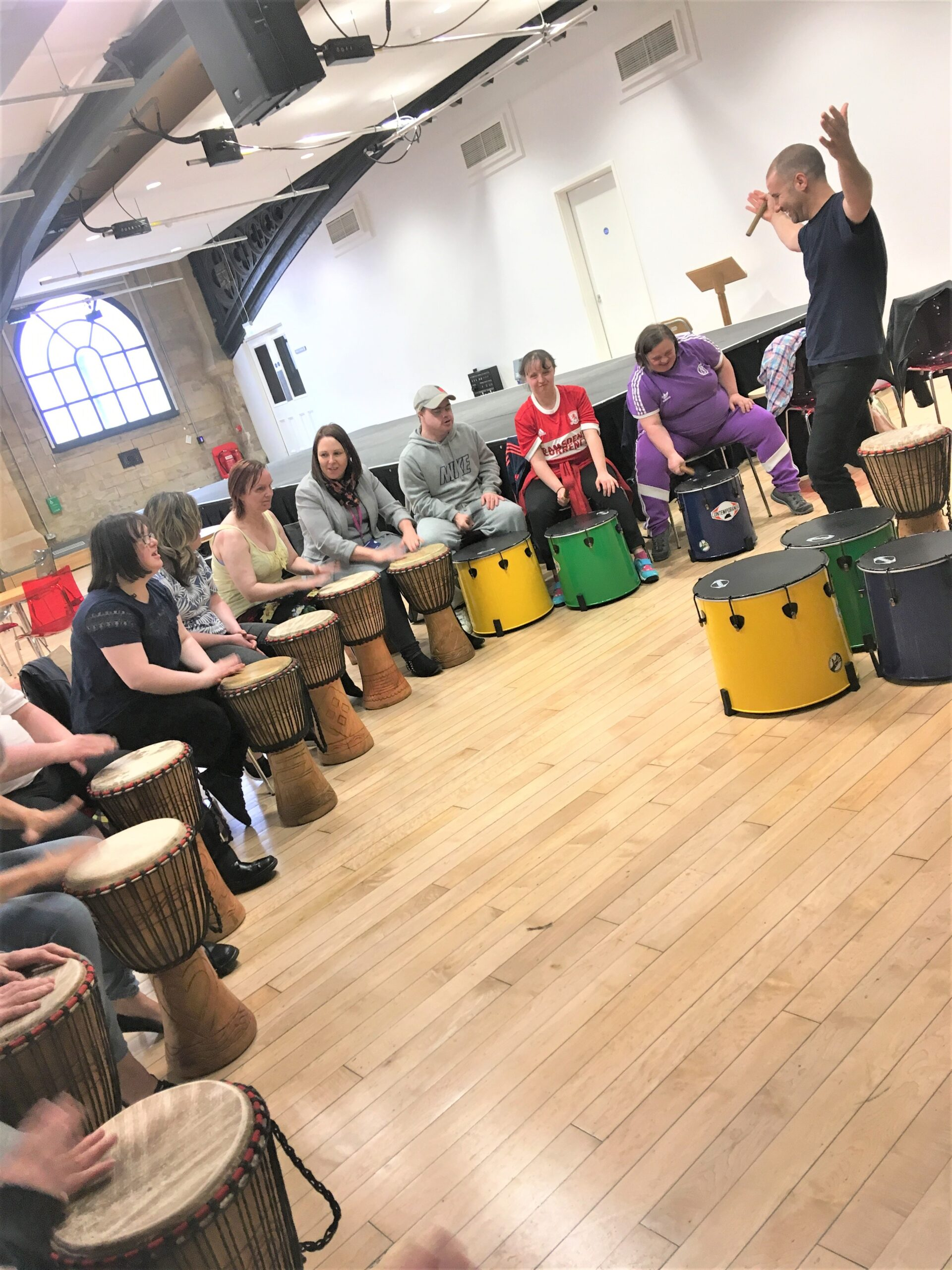 A music leader teaches a group of participants in a drumming workshop