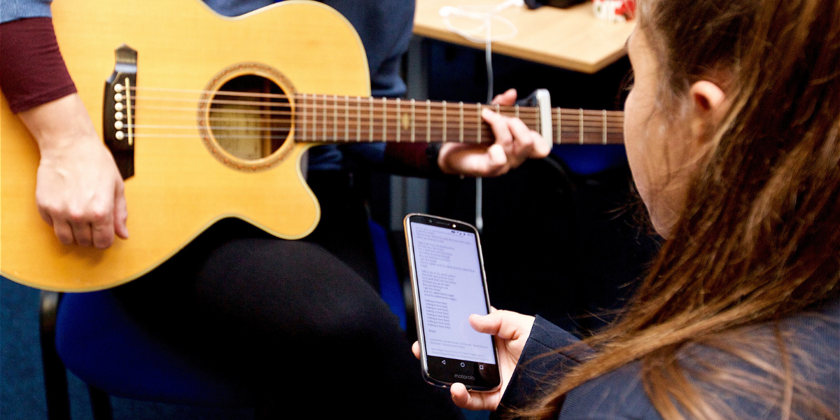 A girl looks at lyrics on her phone whilst someone plays guitar