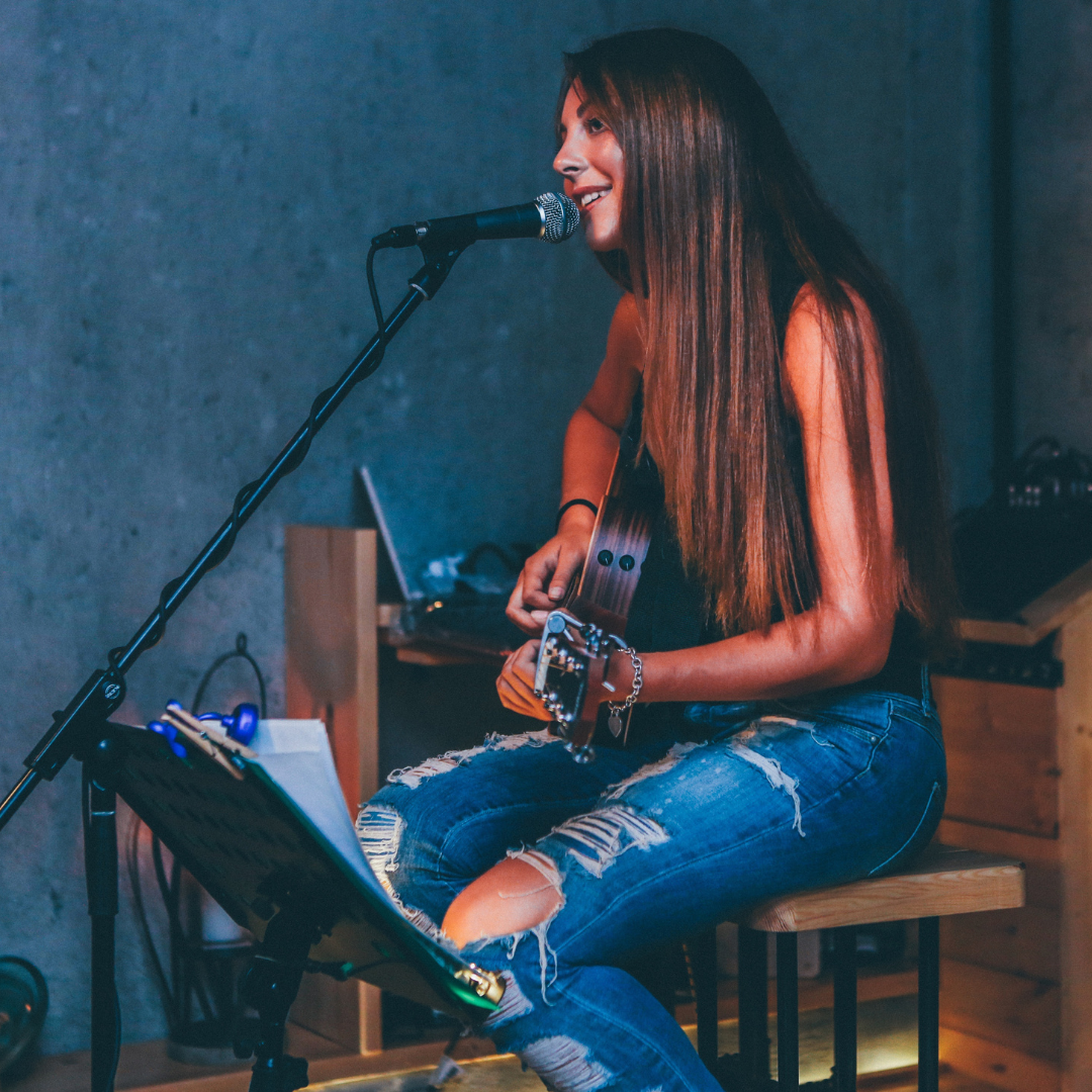 A girl sitting playing an acoustic guitar and singing into a mic