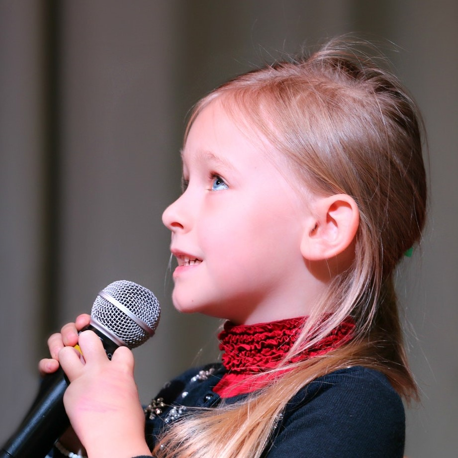 A young girl holding a mic looking up