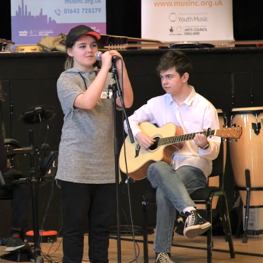 A young girl wearing a cap holding a mic stand. A boy plays guitar in the background.