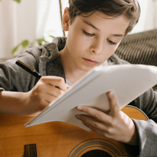A boy writing in a book whilst holding an acoustic guitar
