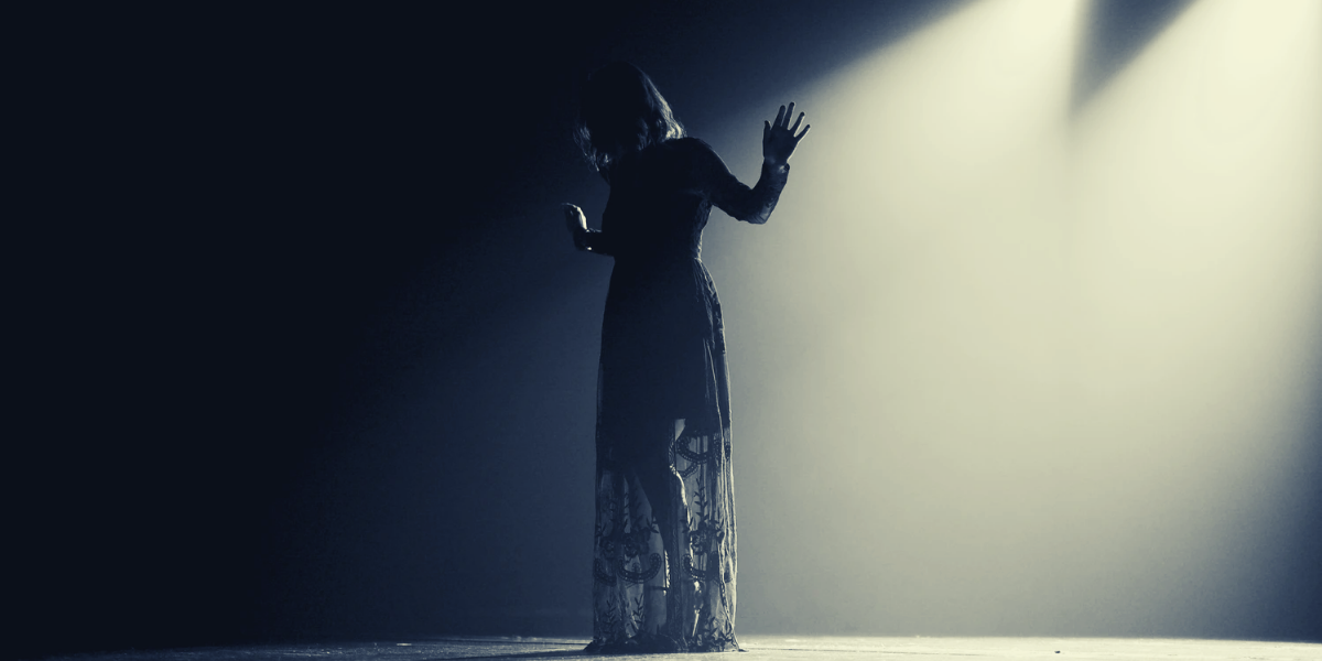 A woman spreading her arms and standing sihouetted under a spotlight on stage
