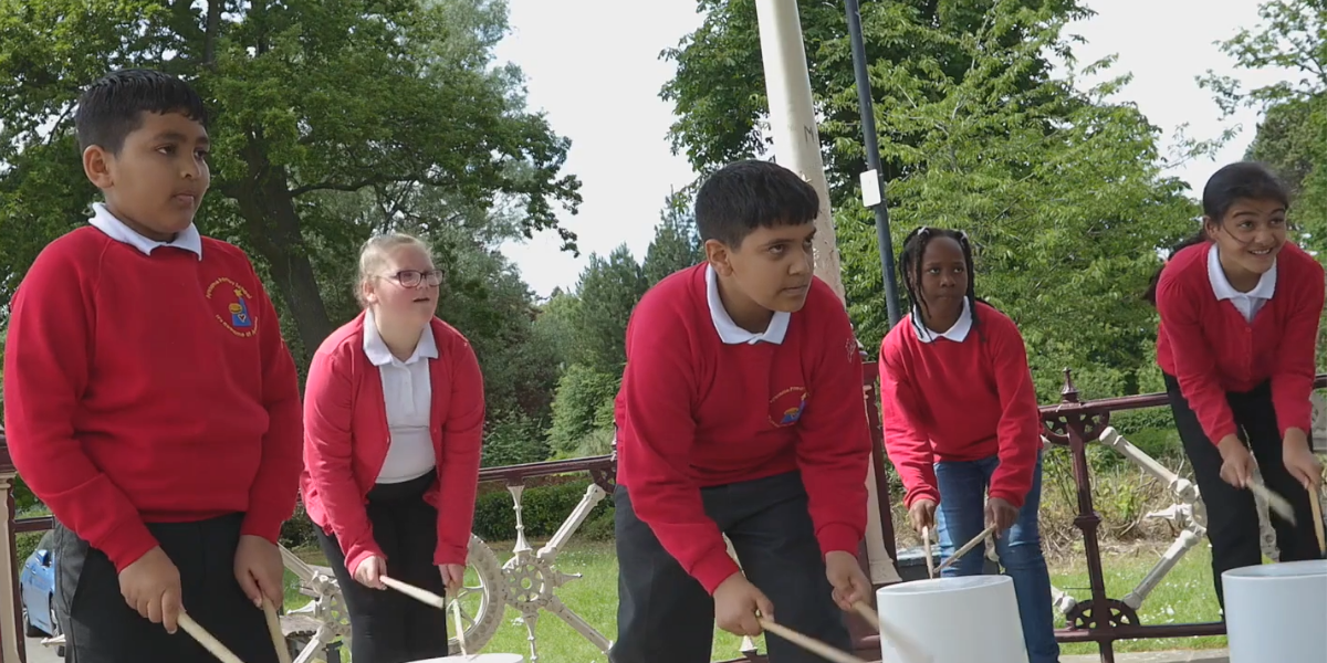 A group of school students drumming outside on upturned buckets