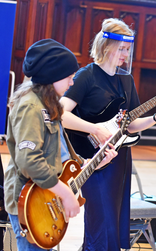 Two young people playing electric guitar