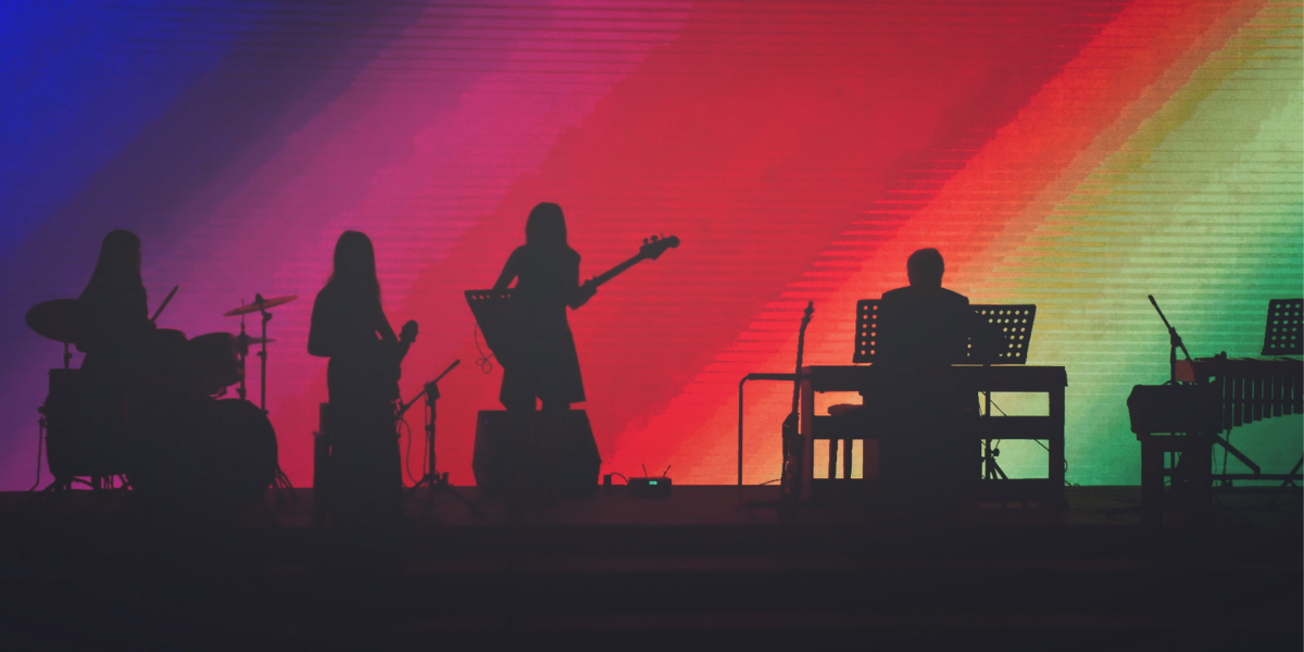 Silhouettes of a band performing on stage wih guitar, bass, drums and keyboard