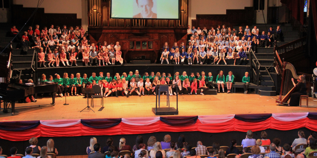 A large group of school children taking part in a concert on the main stage at Middlesbrough Town Hall.