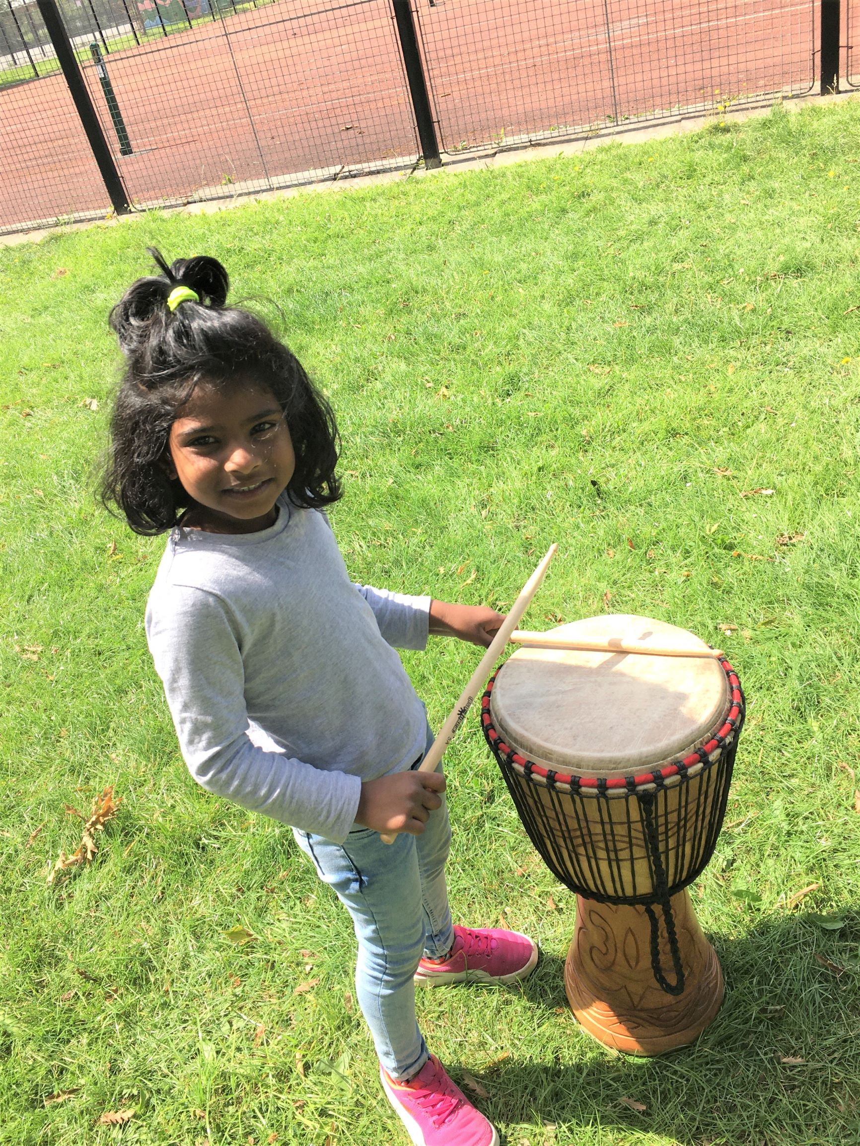 A young girl smiles at the camera and drums on a djembe instrument in the grass